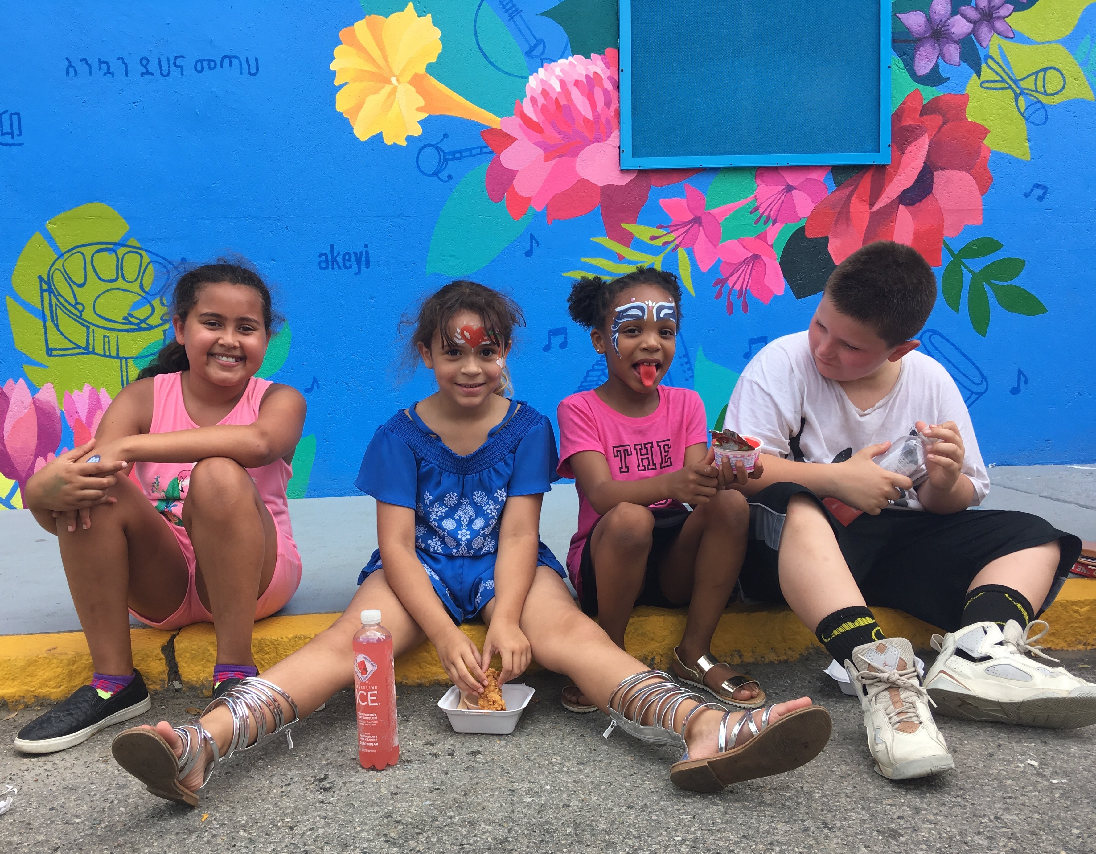 """children sitting in front of """"Together We Thrive"""" Mural, image courtesy of the artist"""